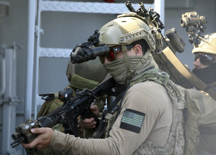 A U.S. Navy SEAL special forces operator, front, and colleagues during a joint U.S.-Cyprus military drill at Limassol port on Friday, Sept. 10, 2021. Cyprus' Defense Minister Charalambos Petrides said the U.S. and Cyprus are on the same strategic path to ensure security and stability in a turbulent region and that continued close cooperation between the special forces of both countries aim to counter threats from potential terrorist acts. (AP Photo/Philippos Christou)