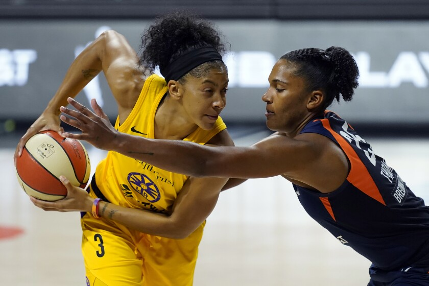 Sparks forward Candace Parker tries to keep the ball away from Connecticut Sun forward Alyssa Thomas.