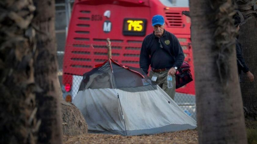 A worker with the Los Angeles Homeless Services Authority checks on a tent pitched near the 101 Freeway in downtown L.A. on Oct. 10.