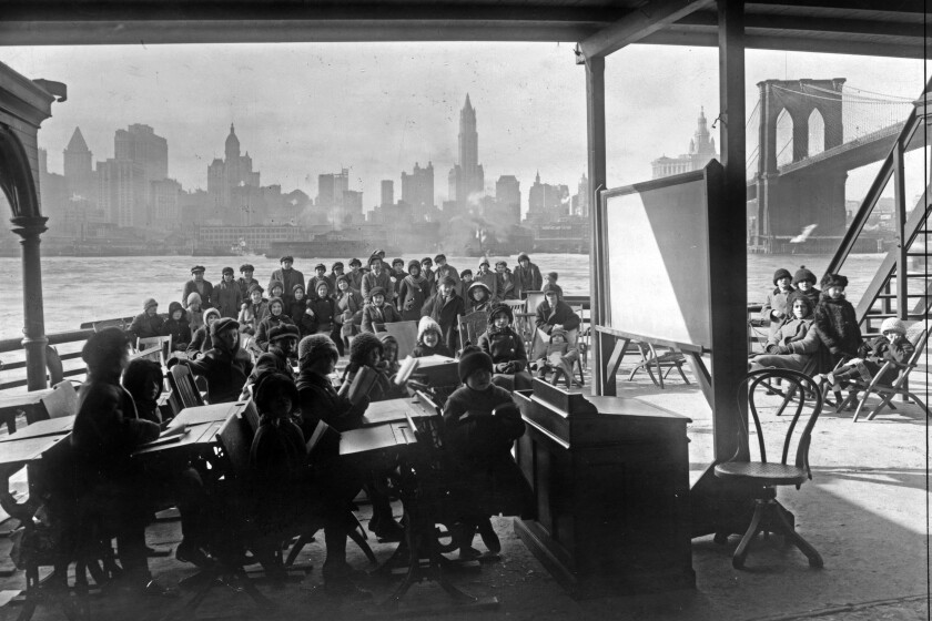 This 1911 photo from the Library of Congress shows schoolchildren on the ferry boat Rutherford, across the river from Manhattan, and near the Brooklyn Bridge, at right, in New York. Poor ventilation in school buildings across the U.S. will limit the ability of in-person instruction to resume safely. Some districts are warming to the idea of outdoor classrooms. (Library of Congress via AP)