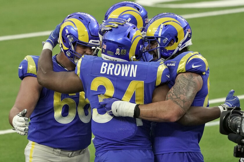 Los Angeles Rams running back Malcolm Brown (34) is hugged by teammates after scoring against the Seattle Seahawks during the second half of an NFL football game Sunday, Nov. 15, 2020, in Inglewood, Calif. (AP Photo/Jae C. Hong)