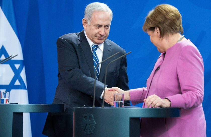 German Chancellor Angela Merkel, right, shakes hands with Israel's Prime Minister Benjamin Netanyahu following their press conference during  the German-Israeli government consultations at the  Chancellery inBerlin, Tuesday Feb. 16,  2016.  (Bernd von Jutrczenka/dpa via AP)