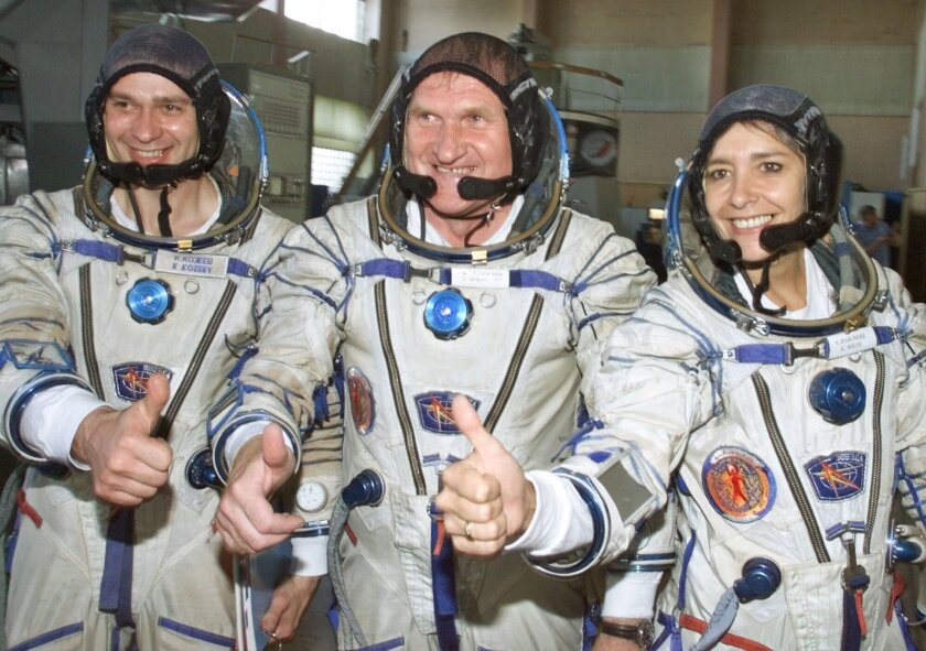 """FILE - In this July 5, 2001 file photo, French astronaut Claudie Haignere, right, and her Russian crewmates Viktor Afanasyev, center, and Konstantin Kozeyev train inside the mock-up of a Soyuz TM spacecraft in Star City. The ESA, NASA's European equivalent. The European Space Agency says it was """"blown away"""" by the record number of applicants – more than 22,000 – hoping to become the continent's next generation of space travelers, including more women than ever and some 200 people with disabilities. AP Photo/Mikhail Metzel, File)"""