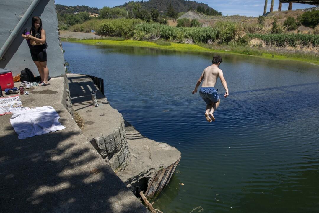 Joseph Lustenberger, 15, jumps off a railroad bridge footing into the Russian River in Healdsburg, Calif.