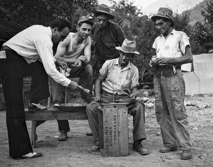 An unidentified gold buyer pays $16 an ounce for dust and tiny nuggets. From his left are Frank Robison, Fire Warden Marshall, Charles T. Brown and M.L. Sims.