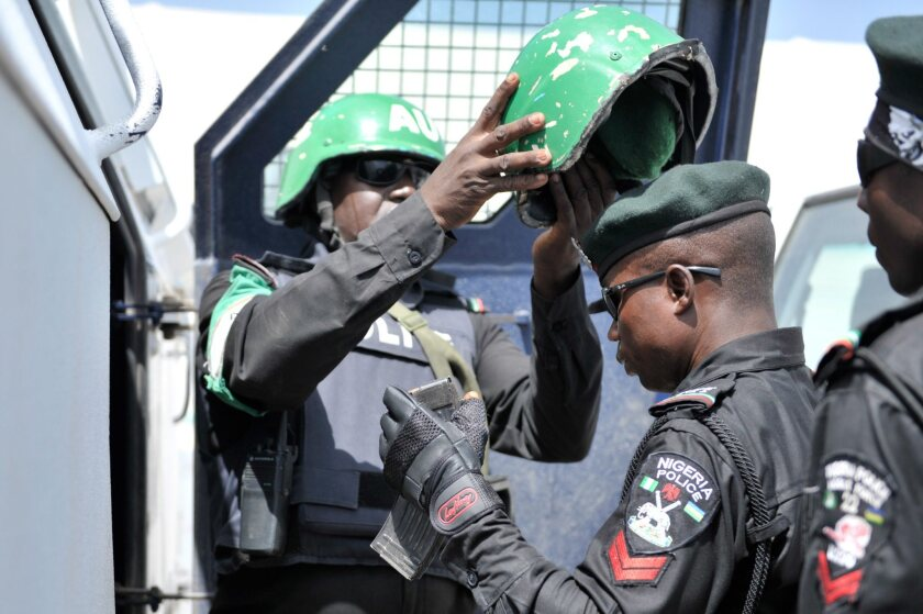 A picture provided by the African Union-United Nations Information Support Team shows a Nigerian police officer receiving an African Union helmet in Mogadishu, Somalia.