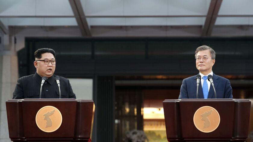 North Korean leader Kim Jong Un, left, speaks as South Korean President Moon Jae-in listens at the b