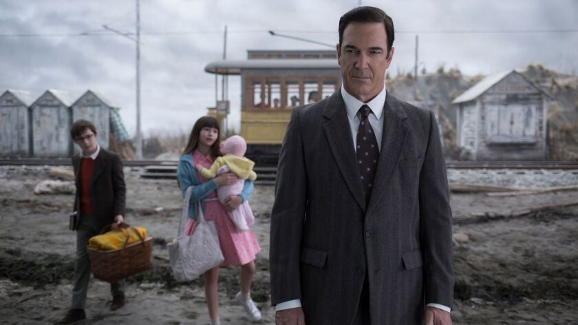 "The Baudelaire orphans (Malina Weissman, Presley Smith, Louis Hynes) and their narrator (Patrick Warburton) in ""Lemony Snicket's A Series of Unfortunate Events."""