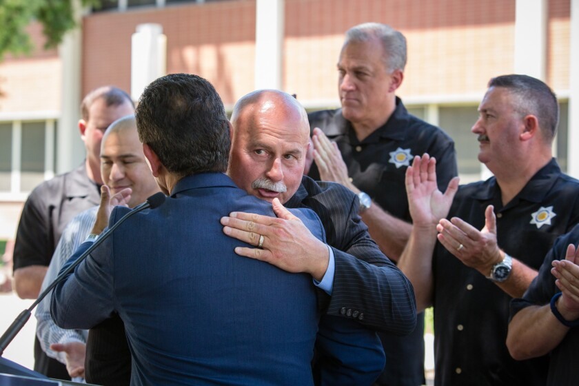Fresno Police Chief Jerry Dyer hugs Antonio Villaraigosa after a 2018 news conference