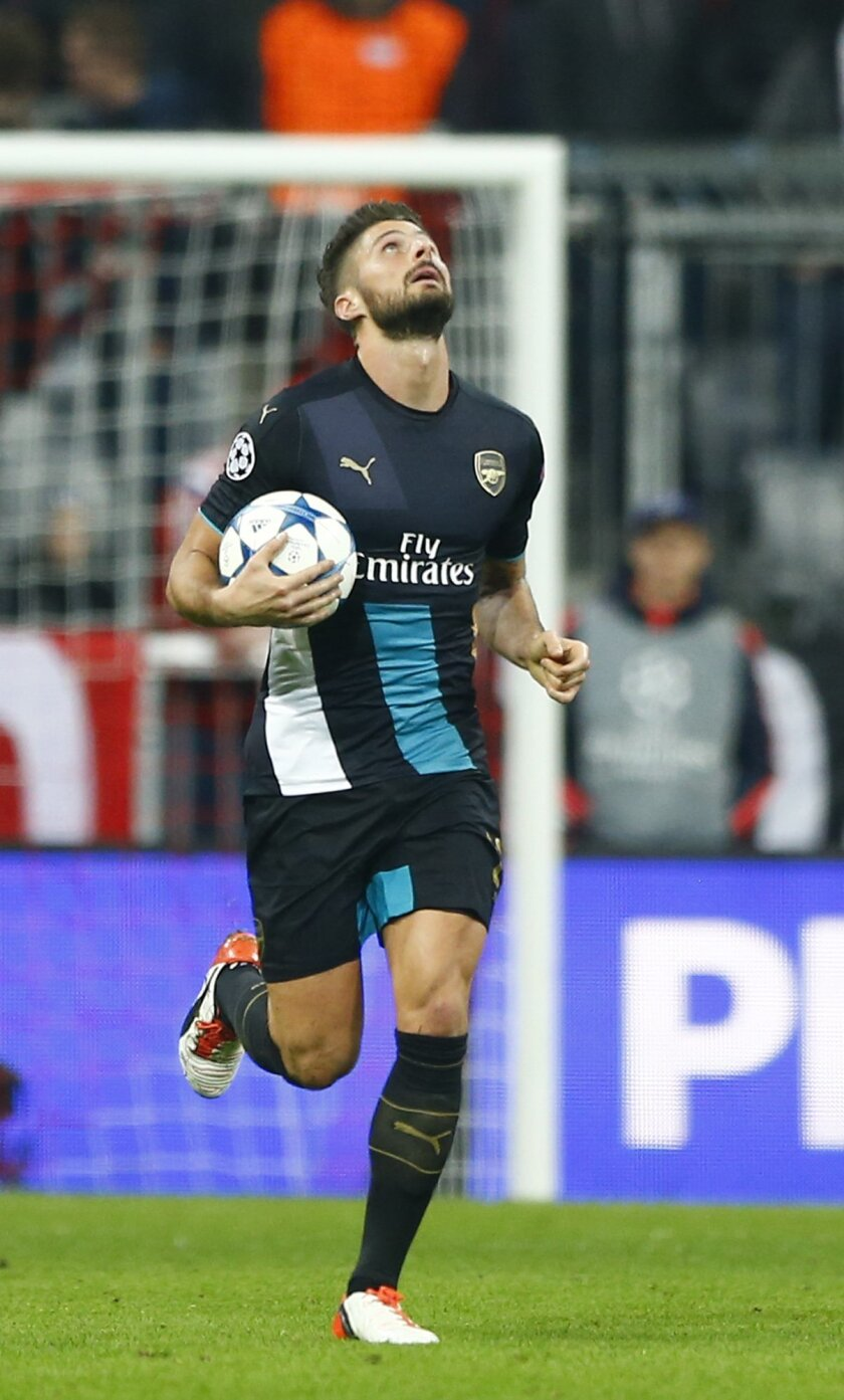 Arsenal's Olivier Giroud carries the ball after scoring his side's first goal during the Champions League Group F soccer match between Bayern Munich and Arsenal FC in Munich, southern Germany, Wednesday, Nov. 4, 2015. (AP Photo/Matthias Schrader)