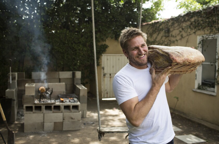 Chef Curtis Stone hefts a piece of meat in the backyard behind his test kitchen in Beverly Hills.