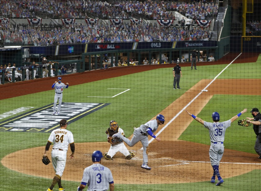 Jason Castro of the San Diego Padres tries but fails to tag out AJ Pollock of the Dodgers.
