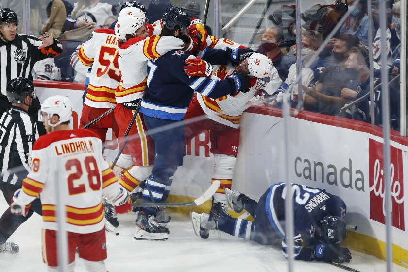 Winnipeg Jets' Adam Lowry (17) grabs Calgary Flames' Blake Coleman (20) after he boarded Jets' Jansen Harkins (12) during the second period of an NHL hockey preseason game Wednesday, Oct. 6, 2021, in Winnipeg, Manitoba. (John Woods/The Canadian Press via AP)