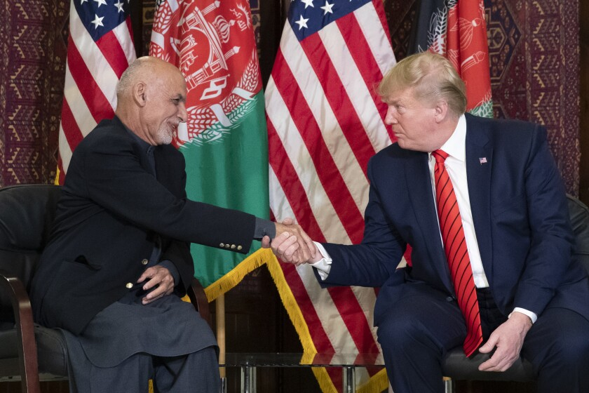 Afghan President Ashraf Ghani, left, and President Trump shake hands while seated in front of their nations' flags on Nov. 28, 2019.