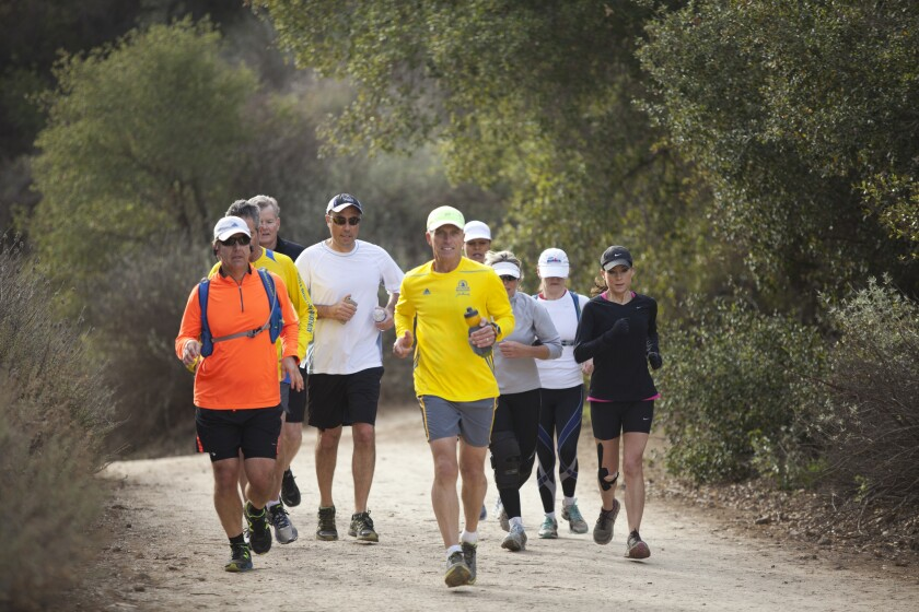Marathoner David Leon Moore, in yellow at center, runs Crags Road in Malibu Creek State Park with a group of friends on a recent Saturday.