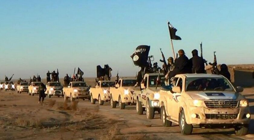 FILE - In this undated file photo released online in the summer of 2014 on a militant social media account, which has been verified and is consistent with other AP reporting, militants of the Islamic State group hold up their weapons and wave its flags on their vehicles in a convoy on a road leadin