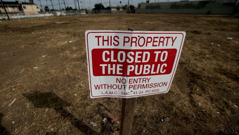 A sign tells passersby not to tresspass on a vacant lot at the intersection of 84th Street and Machester Avenue in South Los Angeles. Vacant lots dot the South L.A. landscape 25 years after the riots.