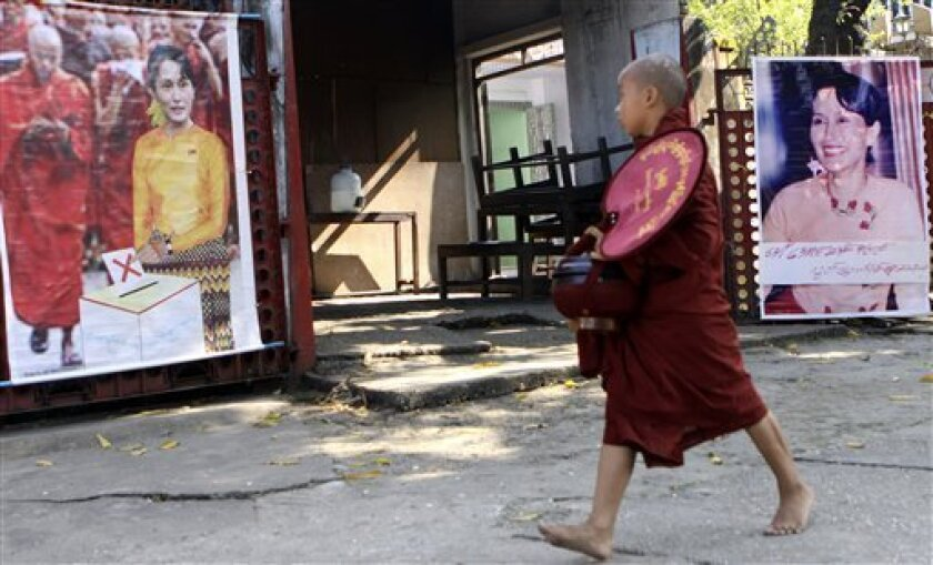 A Buddhist novice walks past posters of detained opposition leader Aung San Suu Kyi, calling not to vote in the upcoming elections outside her National League for Democracy party's headquarters in Yangon, Myanmar. Some of the bigger parties contesting the Nov. 7 elections in military-ruled Myanmar have raised fresh complaints of unfairness, including voters being threatened if they don't back the ruling junta's party. (AP Photo/Khin Maung Win)