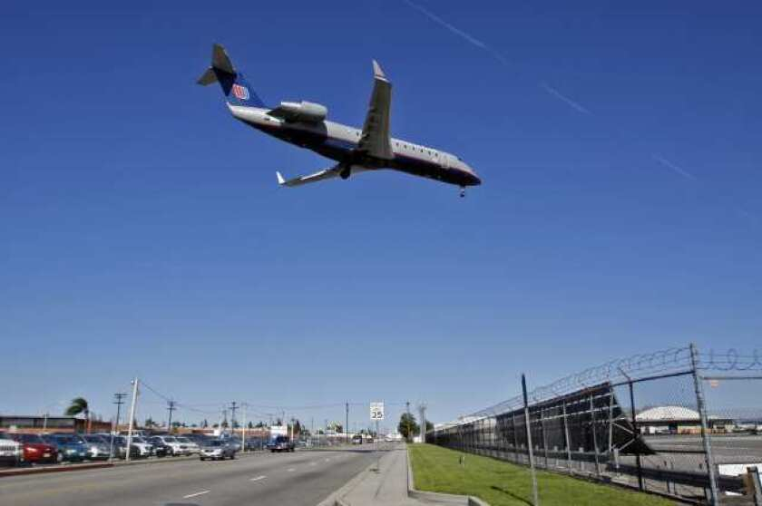 An airplane lands over W. Empire Avenue