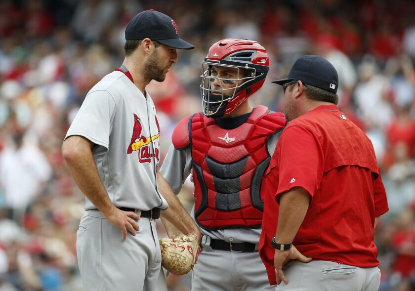 St. Louis Cardinals starting pitcher Michael Wacha, left, catcher Eric Fryer, center, and pitching coach Derek Lilliquist talk on the mound during the fourth inning of a baseball game against the Washington Nationals at Nationals Park, Sunday, May 29, 2016, in Washington. (AP Photo/Alex Brandon)