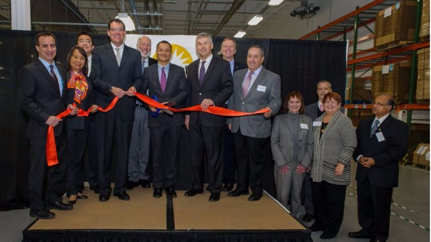 In happier times, officials from Suniva take part in a ribbon-cutting ceremony to mark a manufacturi