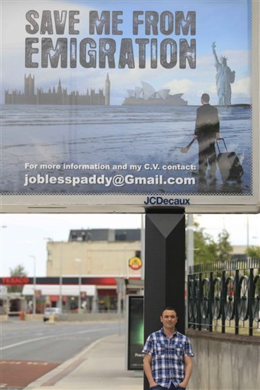 """Féilim Mac An Iomaire stands next to a billboard he paid for in Dublin, Wednesday June 1, 2011. Tens of thousands of Irish people are leaving their debt-shattered land because they can't find work. But one frustrated job hunter, 26-year-old Féilim Mac An Iomaire, has shouted no _ and captured the nation's imagination with an inventive PR offensive that highlights his plight. """"SAVE ME FROM EMIGRATION,"""" reads Mac An Iomaire's billboard in the heart of Dublin, the focal point for a novel social media-driven campaign that highlights his eight-month search for work and desire to stay in Ireland. The effort has cost him about €2,000 ($2,800) _ and given him a priceless global spotlight for his skills as a marketer and deal-maker. (AP Photo/Peter Morrison)"""