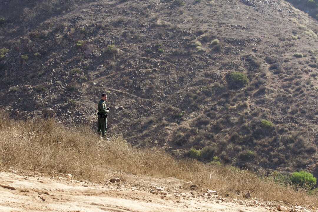 US Border Patrol Agent Theron Francisco looked off in to the Otay Mountain Wilderness Area where the border fence will be constructed in the coming year, at the US-Mexico Border east of Otay Mesa in San Diego on Tuesday, October 15, 2019.