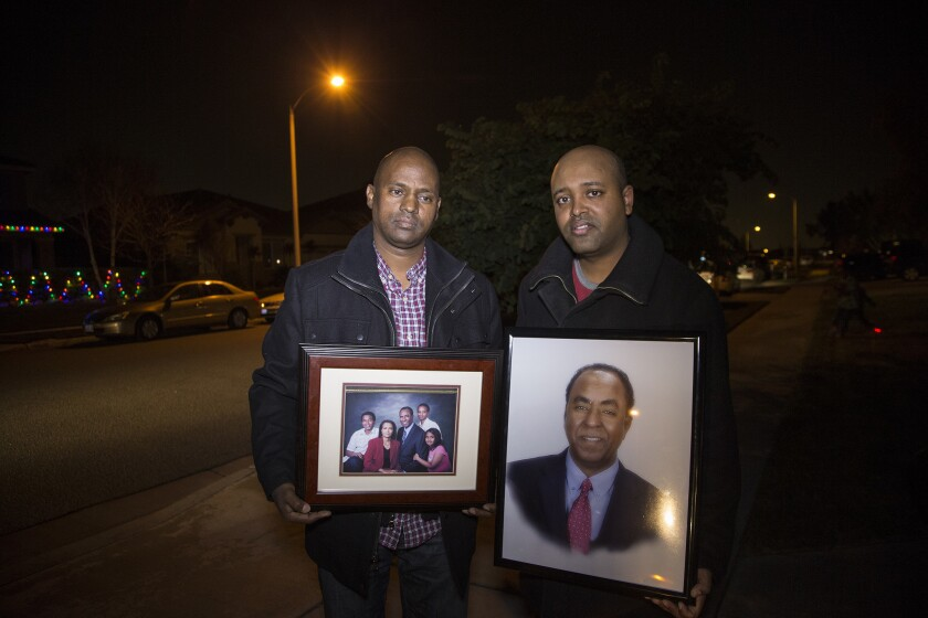 Berhane Gebreslassie, left, brother of shooting victim Isaac Amanios, and Zeke Gebrekidane, nephew, with family photos outside the family's home in Fontana.