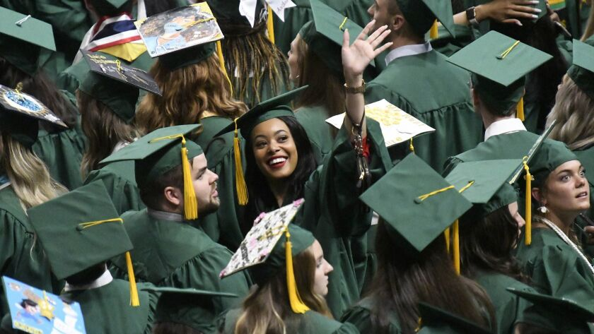 UNC Charlotte graduating seniors wave to friends and family. Americans with a bachelor's degree earned less in real terms last year than in 1990, according to the New York Fed.