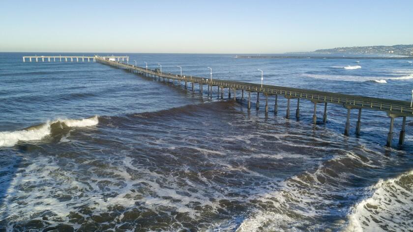 Waves roll under the Ocean Beach Pier in January 2020.