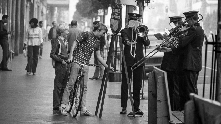 Dec. 20, 1971: Youth on bicycle drops some change into Salvation Army kettle located at corner of Ho