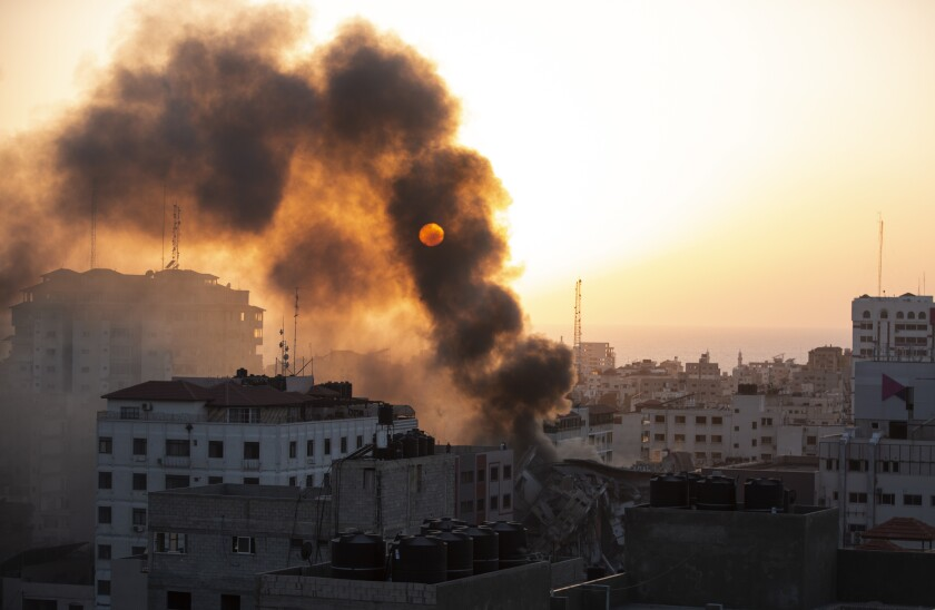 Smoke blocks out the sun above a collapsed building in Gaza