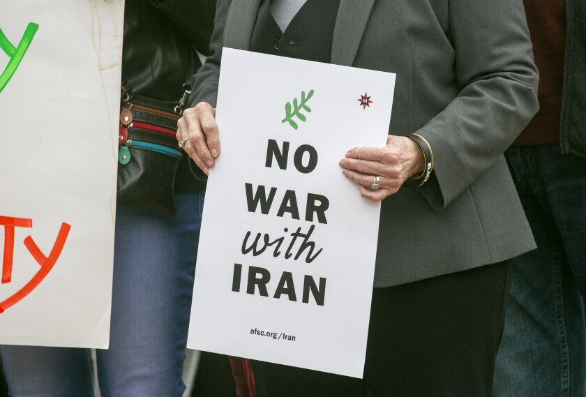 Signs being held at a press conference that included religious leaders and community activists speaking out against a war with Iran on Wednesday, January 8, 2020 in Balboa Park.