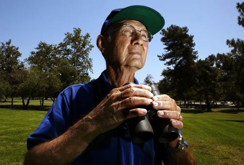 In blue hat and blue shirt, 80-year-old Dick Purvis observes bluebirds hovering near the boxes he has placed in trees at Mile Square Park in Fountain Valley. Purvis and a large group of volunteers are placing boxes in trees throughout Orange County to help repopulate the birds.