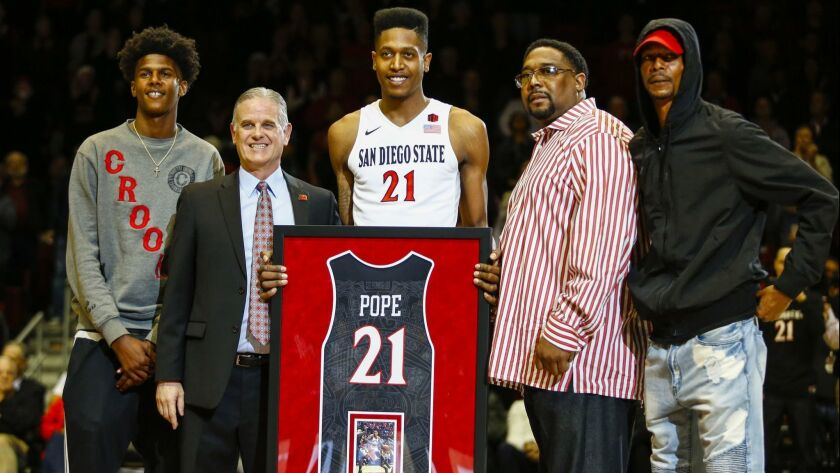 Malik Pope, shown here on Senior Night at SDSU with his family and coach Brian Dutcher, has signed with a pro club in Greece.