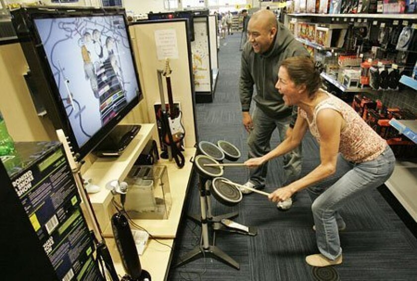"""Paul Clark (center) helped fellow shopper Kelley Donnelly learn to play """"Rock Band"""" on a Microsoft Xbox 360 gaming system yesterday at Best Buy in Mission Valley. (John Gibbins / Union-Tribune)"""