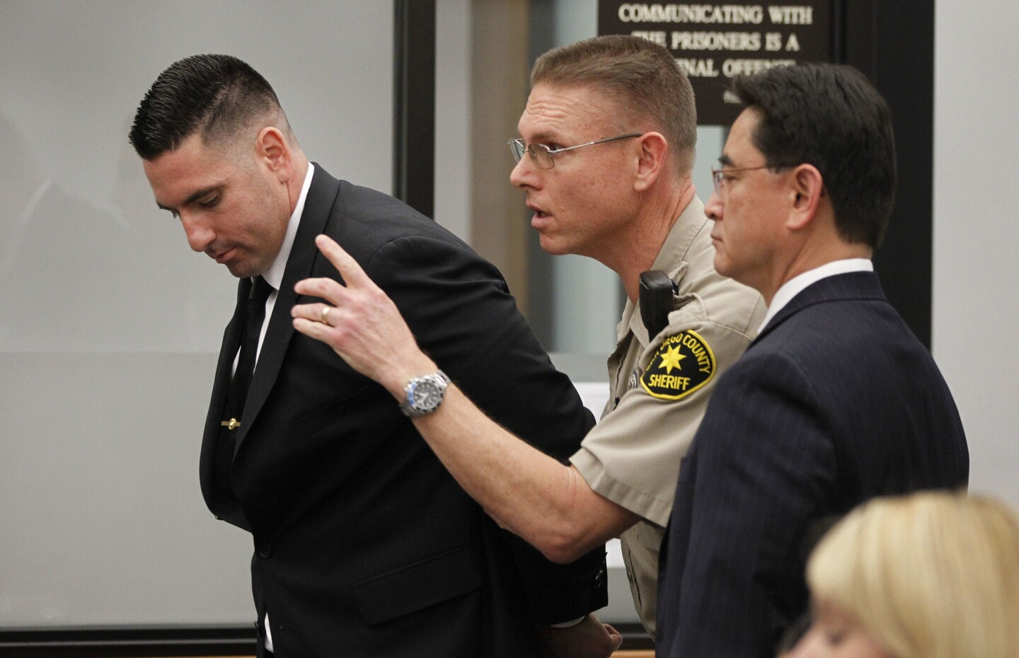 After being handcuffed, former Deputy Richard Fischer, left, is directed out of the courtroom by a court bailiff as he is taken into custody after his arraignment at the Vista courthouse on Thursday.
