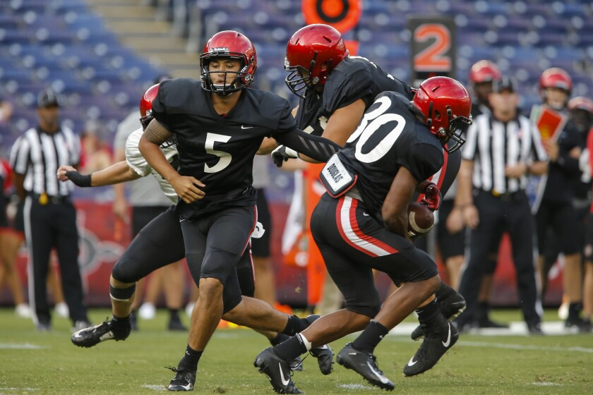 San Diego State quarterback Mark Salazar hands off to running back Justin Dinka in the third quarter of Saturday night's scrimmage at SDCCU Stadium. Salazar suffered a knee injury later in the scrimmage.