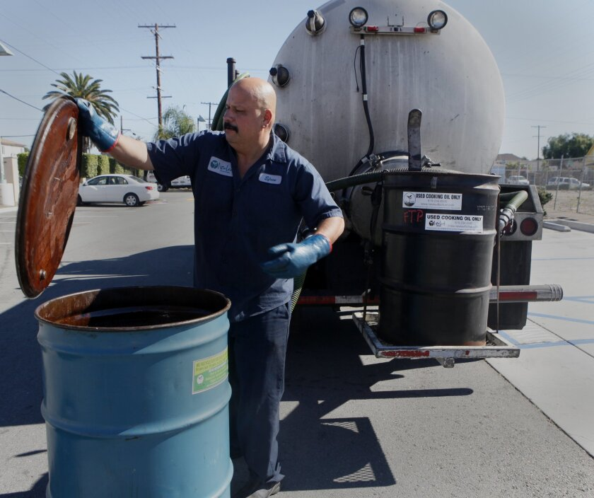 In a 2016 file photo, Efren Montoya of New Leaf Biofuel collects used cooking oil to be converted into biodiesel at the company's Barrio Logan facility. It will fuel large diesel trucks.