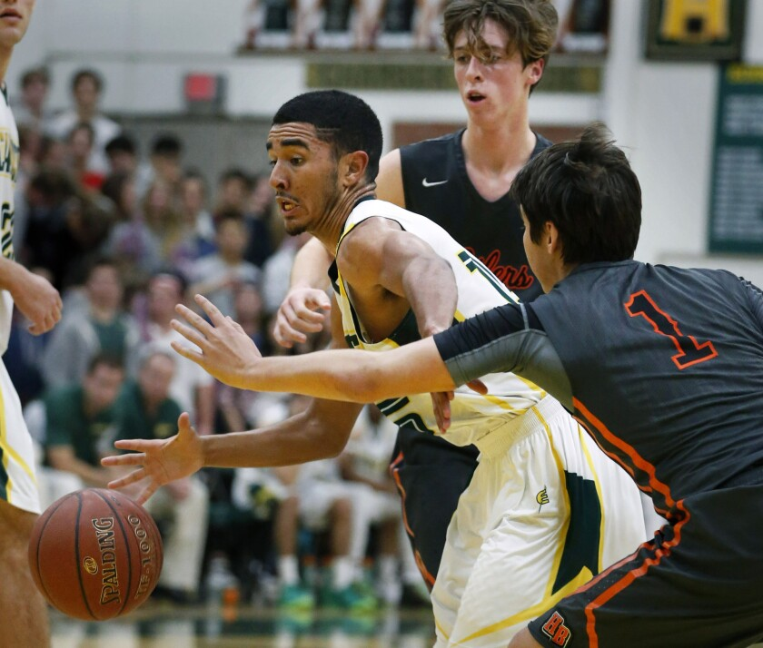 Edison guard Nate Matthews is double-teamed by Huntington Beach's Sean Strom (1) and Fletcher Wilson in a Sunset League basketball game on Friday.