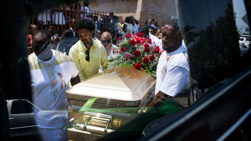 Pallbearers carry the casket of DeAndre Hughes into a hearse in Compton. His mother, Barbara Pritchett-Hughes, said her mind instantly flashed back to nine years earlier when her 15-year-old son, Dovon Harris, was fatally shot in Watts.