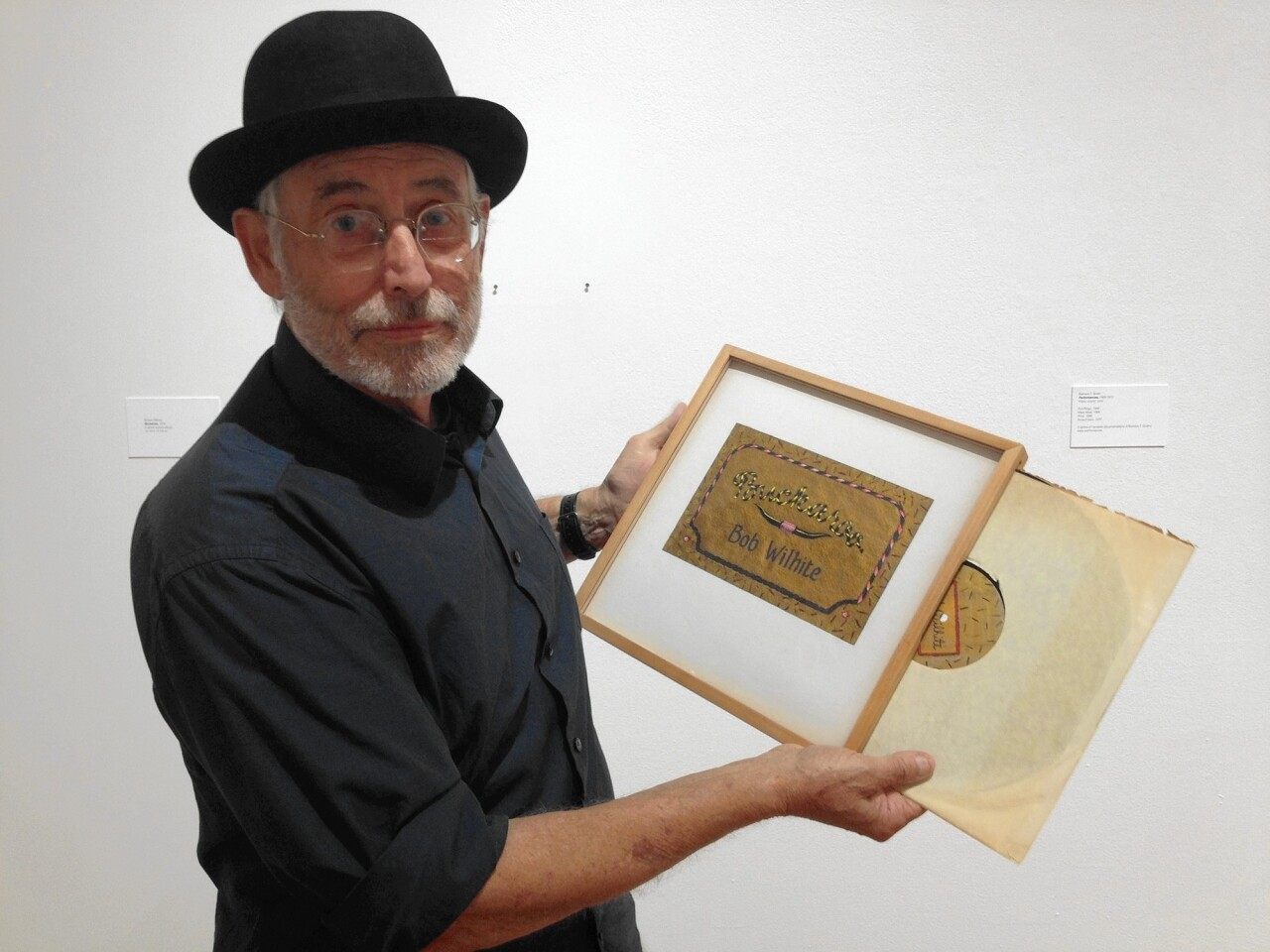 """Artist and UC Irvine graduate Robert Wilhite demonstrates how his 1976 artwork, """"Buckaroo,"""" is actually a handmade record case with a real vinyl record inside. His work is on view in the University Art Gallery through Dec. 12."""