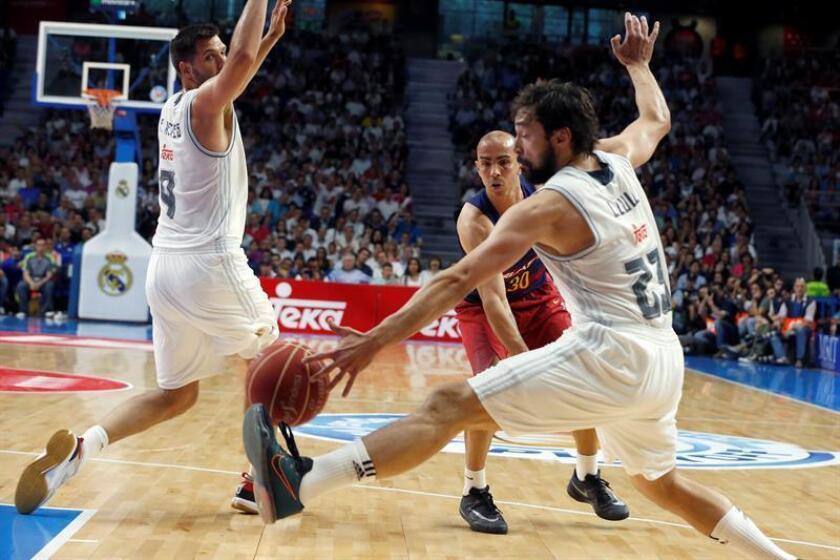 El base portorriqueño Carlos Arroyo (c), centra el balón entre Sergio LLull (d) y Felipe Reyes (i), del Real Madrid, durante el cuarto partido de la final de la Liga ACB. EFE/Archivo