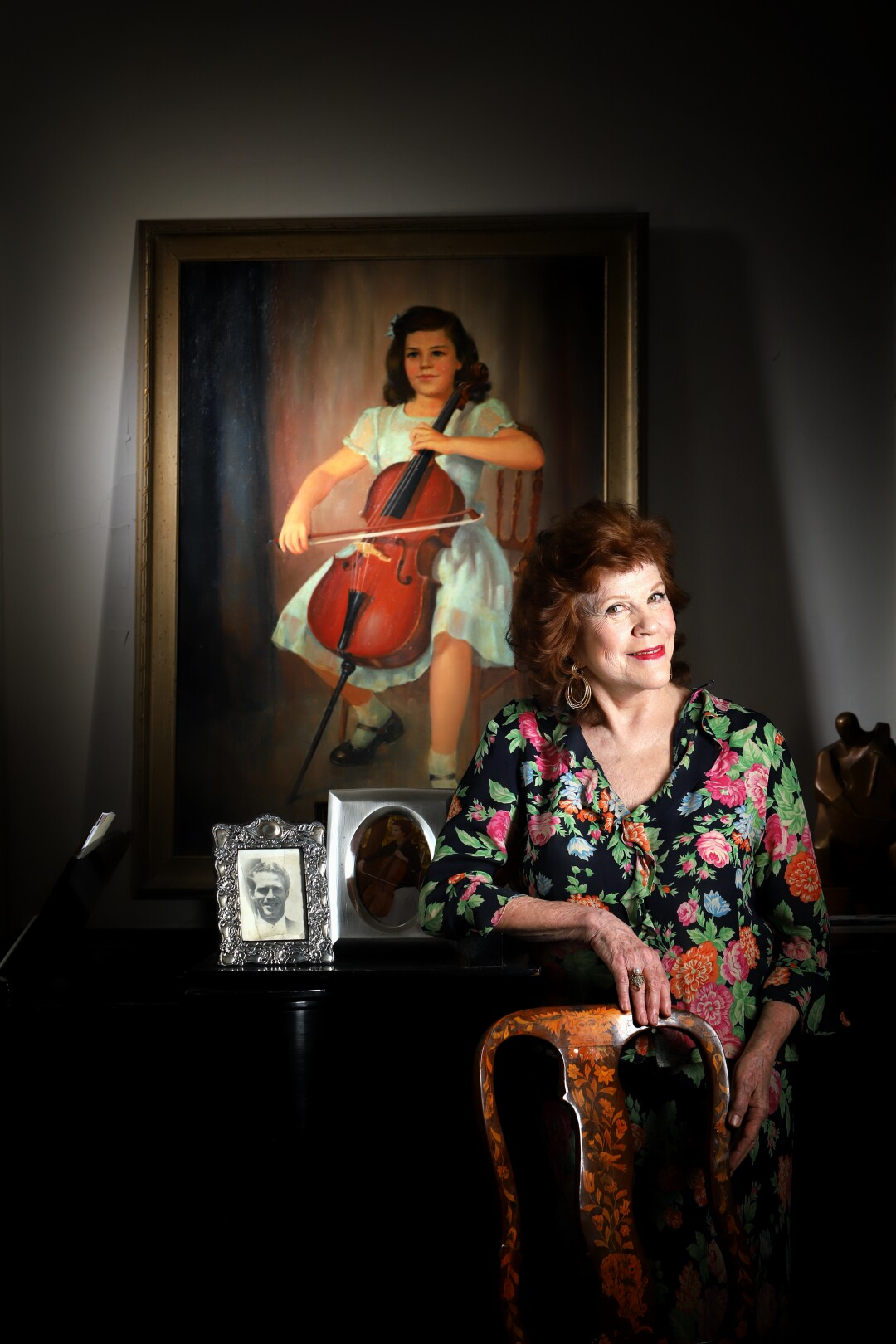 Christine Walevska stands in her Manhattan home alongside a portrait of herself as a child with her Bernardel cello.