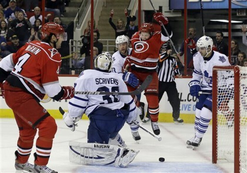 Carolina Hurricanes' Jeff Skinner (53) leaps following Jordan Staal's goal against the Toronto Maple Leafs during the second period of an NHL hockey game in Raleigh, N.C., Thursday, Feb. 14, 2013. Maple Leafs goalie Ben Scrivens (30), Mike Kostka and Nazem Kadri, right, watch with Hurricanes' Jamie