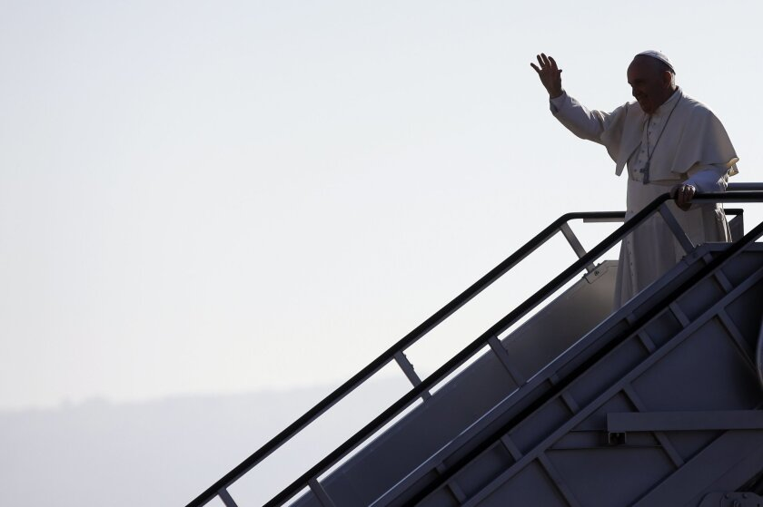 Pope Francis waves upon his arrival at the airport in Tuxtla Gutierrez, Mexico, Monday, Feb. 15, 2016. Francis is celebrating Mexico's Indians on Monday with a visit to Chiapas state, a center of indigenous culture, where he will preside over a Mass in three native languages thanks to a new Vatican