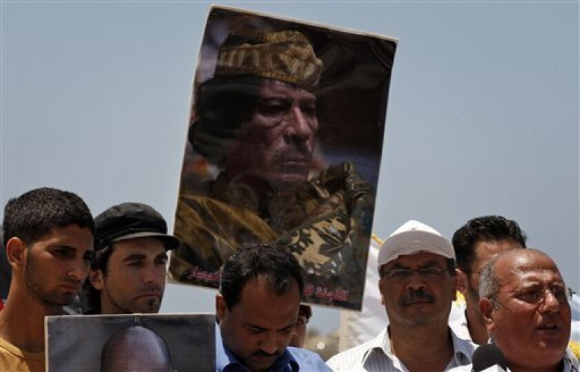 Palestinians hold a poster of the Libyan leader Moammar Gadhafi during a rally to support a Libyan ship making its way towards Gaza in the latest attempt to thwart an Israeli naval blockade, in Gaza City, Wednesday, July 14, 2010. Flanked by Israeli missile boats, a Libyan charity's aid ship was sa