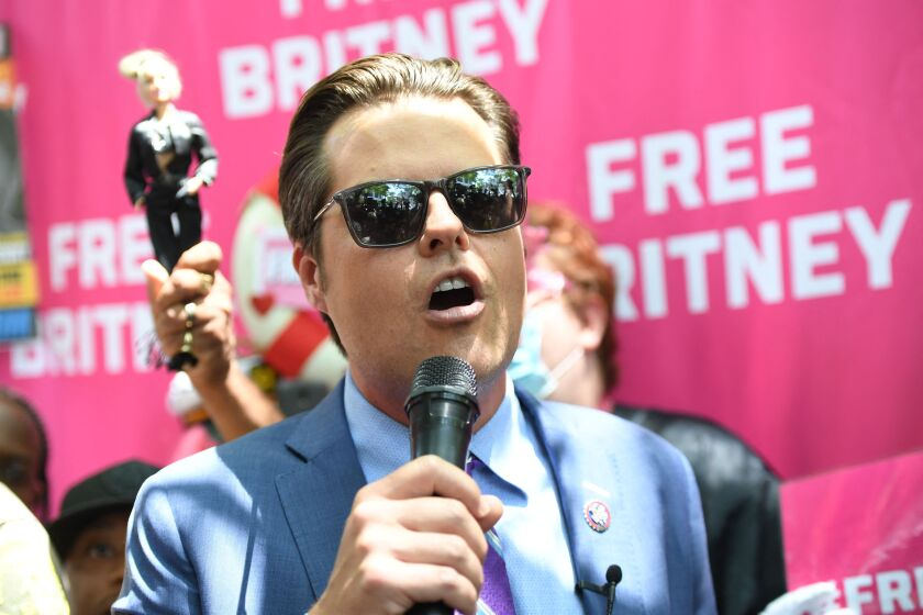A man in a blue suit speaks into a microphone in front of a pink Free Britney backdrop