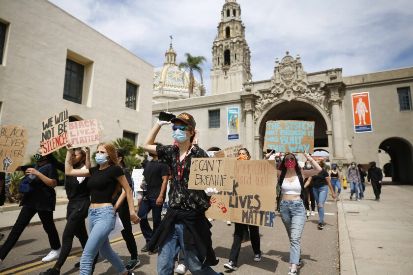 Youth protesters peacefully march Monday through Balboa Park. They were protesting police brutality and the recent death of George Floyd.