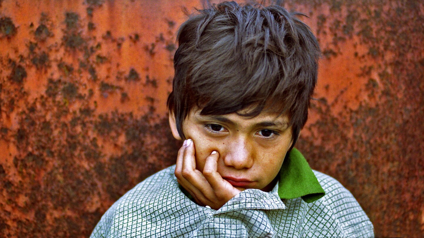 Denis Contreras, 12, awakens after sleeping in a gravel-filled hopper car in a Tapachula, Mexico, rail yard in August 2000. His mattress was crumpled paper, his blanket an oversize pullover.